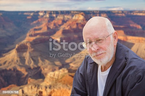 Happy Senior Man Posing on the Edge of The Grand Canyon.