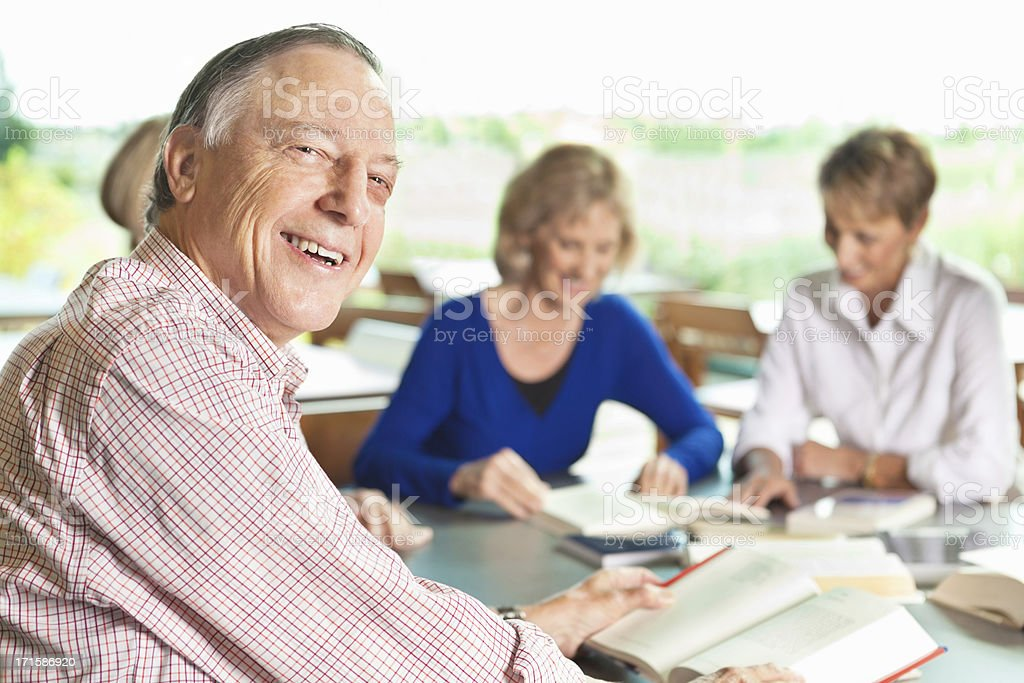Happy senior man reading at table in library stock photo