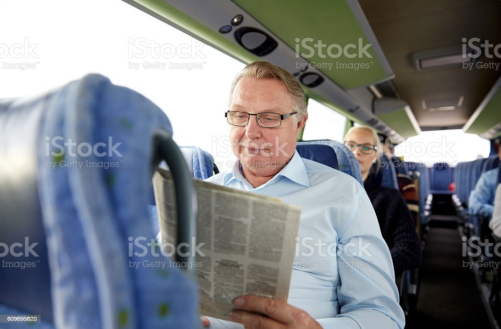 happy senior man reading newspaper in travel bus stock photo