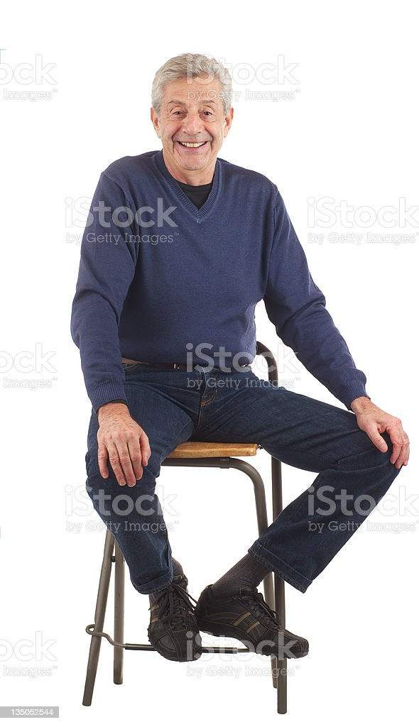 Happy senior man sits with hands on knees. stock photo