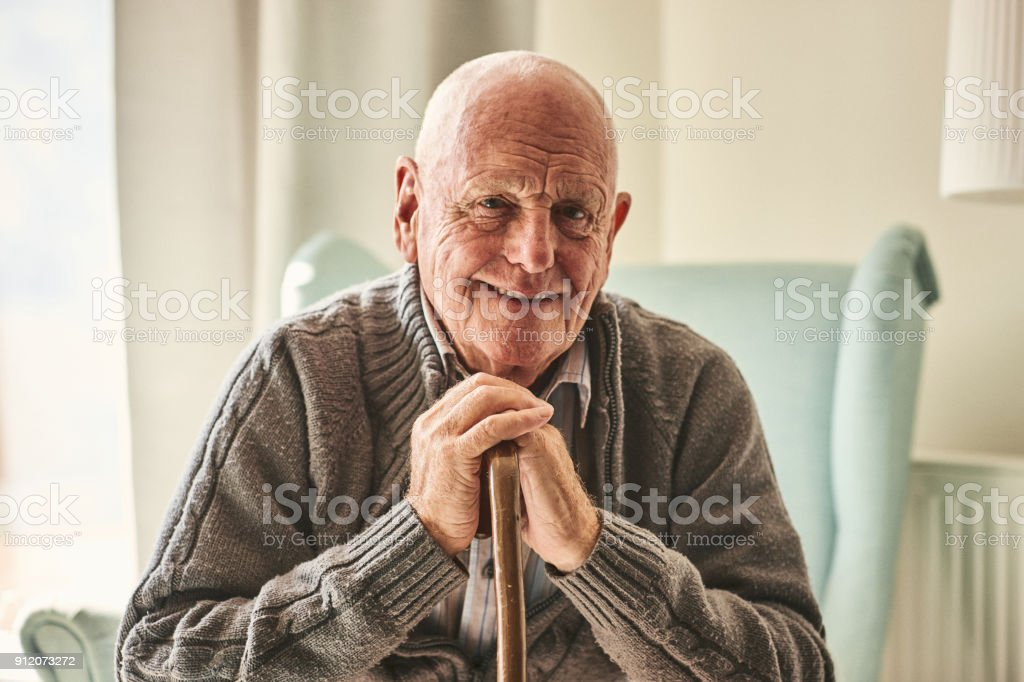 Happy senior man sitting at home stock photo