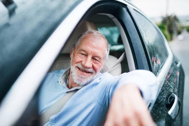 happy senior man sitting in car in driver seat. - old men window imagens e fotografias de stock