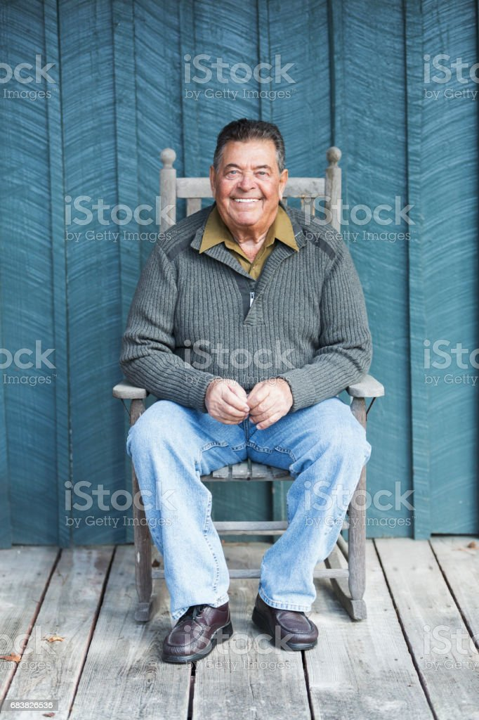 Happy senior man sitting in rocking chair on porch stock photo