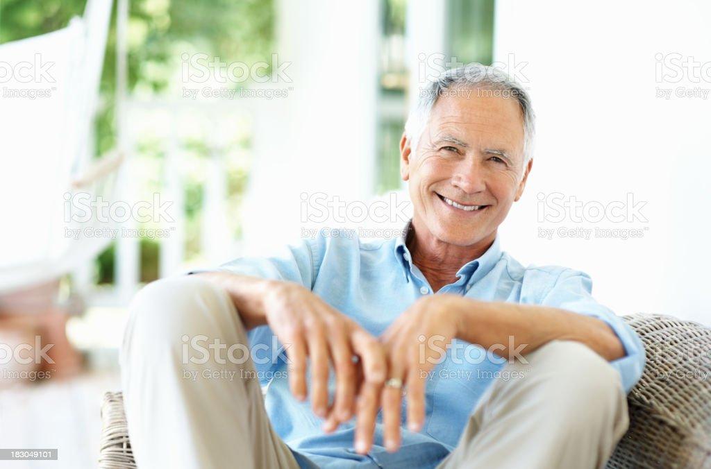 Happy senior man sitting on wicker chair smiling stock photo