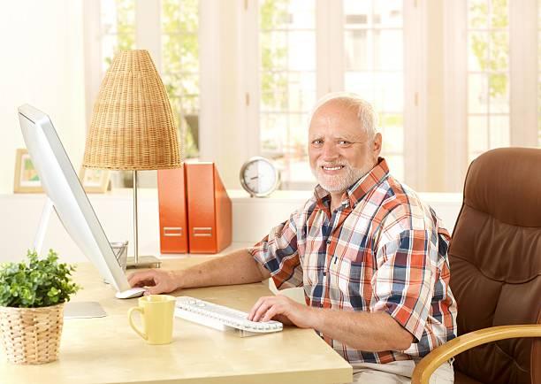 Happy senior man using computer stock photo