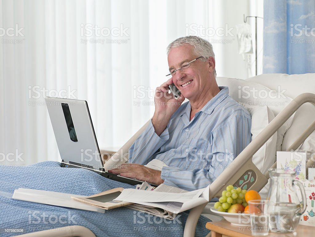 Happy senior man using mobile phone and laptop at hospital bed royalty-free stock photo