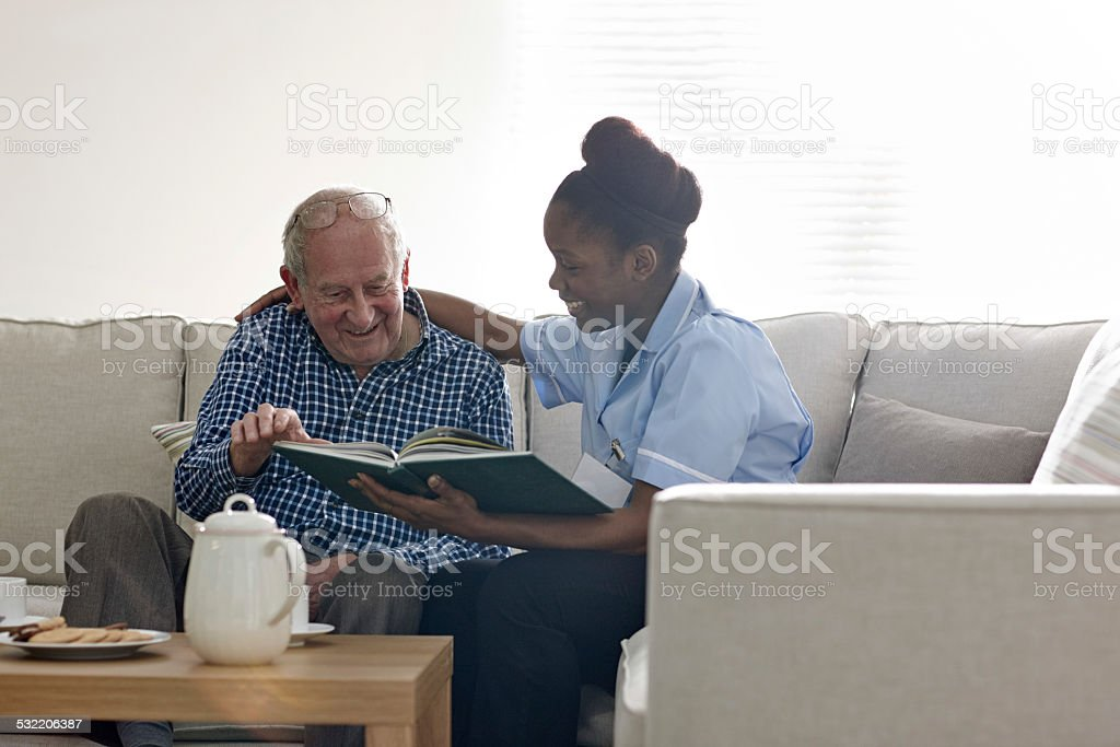 Happy senior man with carer reading a novel together stock photo