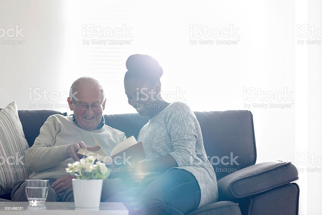 Happy senior man with female carer reading a book stock photo