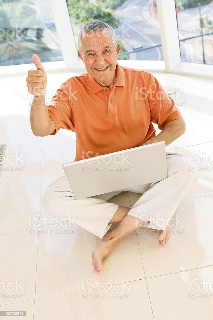Happy senior man with laptop and gesturing thumbs up royalty-free stock photo