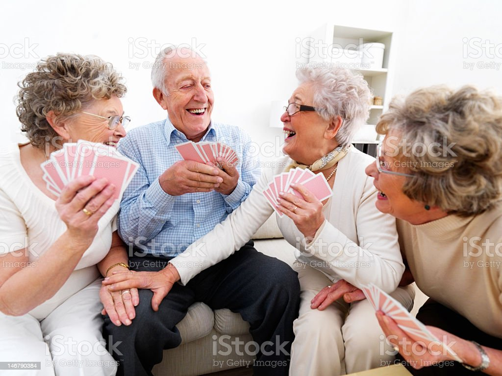 Happy senior men and women playing cards stock photo