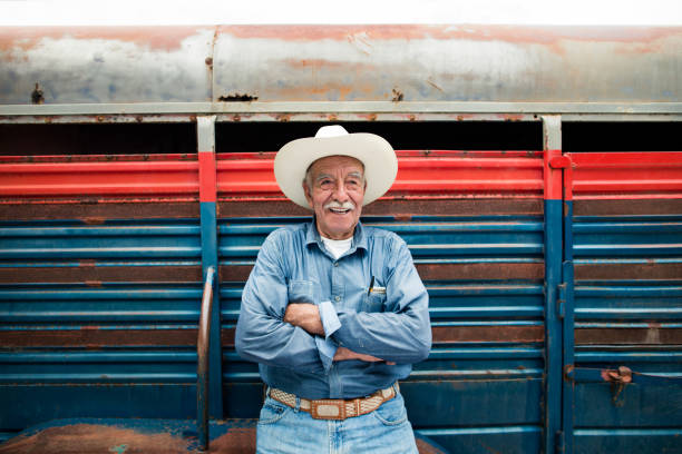 Happy senior mexican man standing with arms crossed stock photo