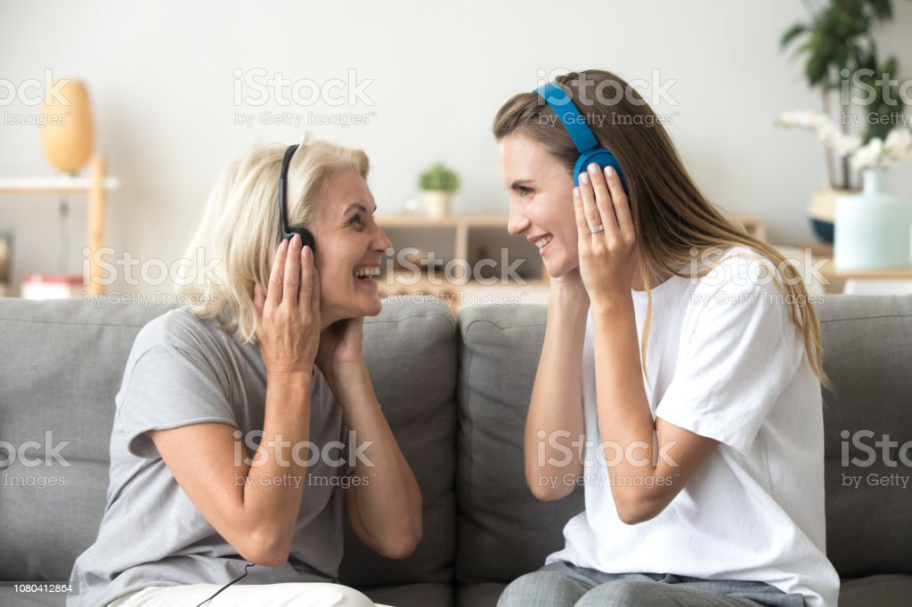Happy senior mother and adult daughter laughing listening to music in...