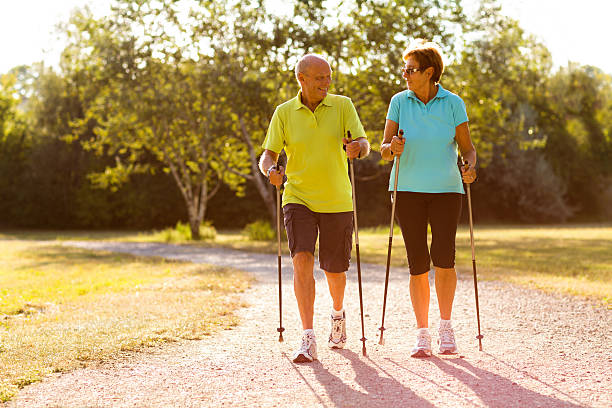 happy senior nordic walking couple happy senior couple nordic walking on path in park nordic walking stock pictures, royalty-free photos & images