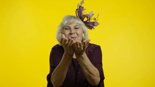 glückliche senior alte frau sendet luftfliegen küsse in die kamera, zeigt liebe, romantische emotionen - sexy granny stock-fotos und bilder