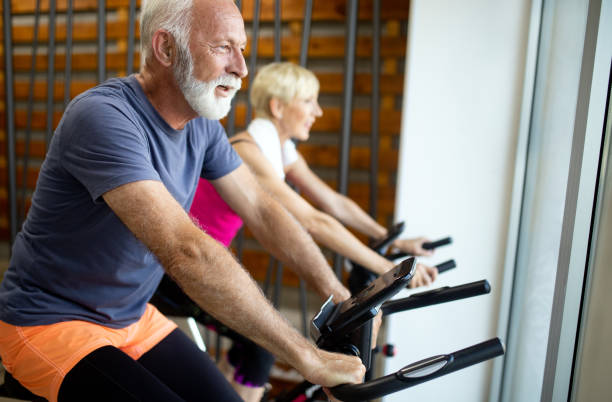 Happy senior people doing indoor biking in a fitness club Happy mature people doing indoor biking in a fitness club exercise bike stock pictures, royalty-free photos & images