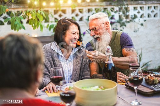 Happy senior people having fun at barbecue dinner - Multiracial mature friends eating at bbq meal - Food, friendship, relationship and summer lifestyle concept - Focus on asian woman face