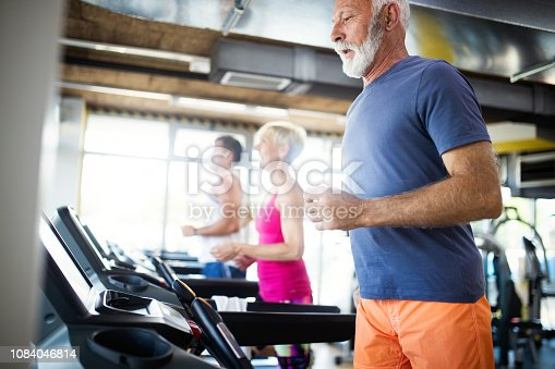 Happy mature people running together on treadmills in gym.