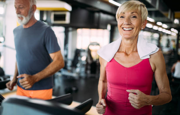 happy senior people running together on treadmills in gym. - active lifestyle stock pictures, royalty-free photos & images