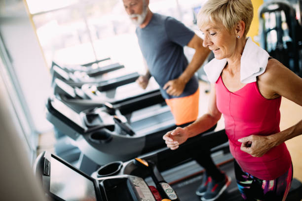Happy senior people running together on treadmills in gym. stock photo