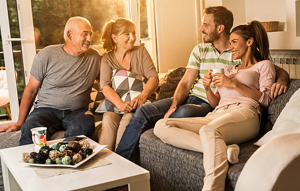 Happy senior people talking to young couple at home. – Foto