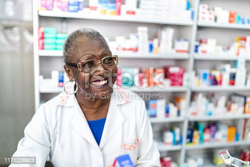 Happy senior pharmacist supporting a customer