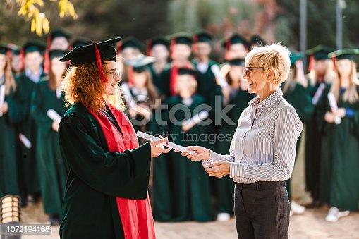 istock Happy senior professor giving diploma to female student on graduation day. 1072194168