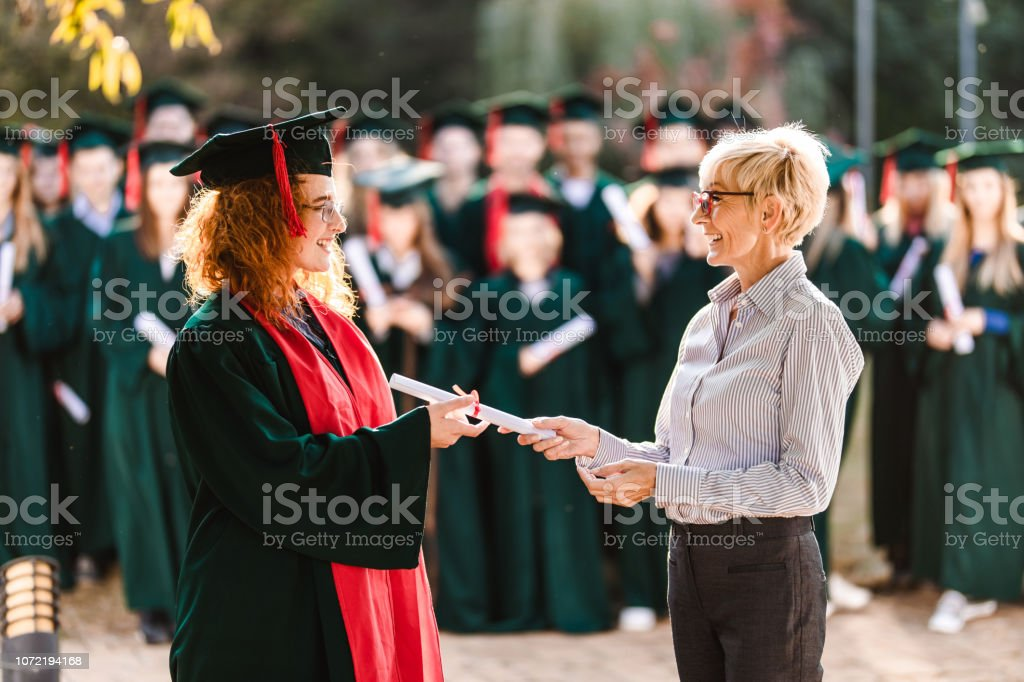 Happy senior professor giving diploma to female student on graduation day. stock photo