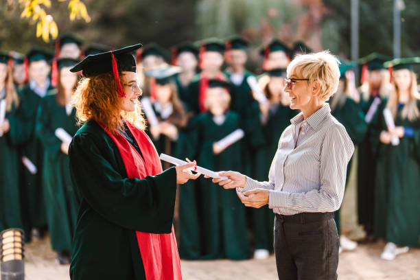 Happy senior professor giving diploma to female student on graduation day. Happy female student talking to her professor while receiving certificate on graduation day. alumnus stock pictures, royalty-free photos & images