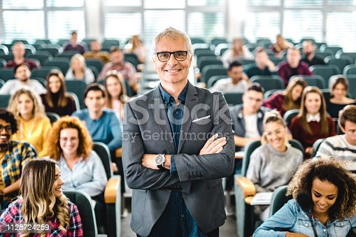 Happy mature professor standing in a full lecture hall with his arms crossed and looking at camera.