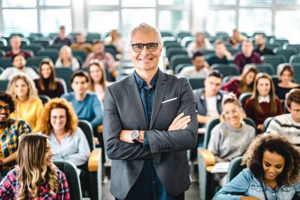 happy senior professor with large group of students in a lecture hall. - professore foto e immagini stock