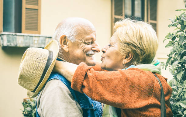 happy senior retired couple having fun kissing outdoors at travel vacation - love concept of joyful elderly and retirement lifestyle with man lovely watching wife in the eyes - bright vintage filter - falling in love stock pictures, royalty-free photos & images