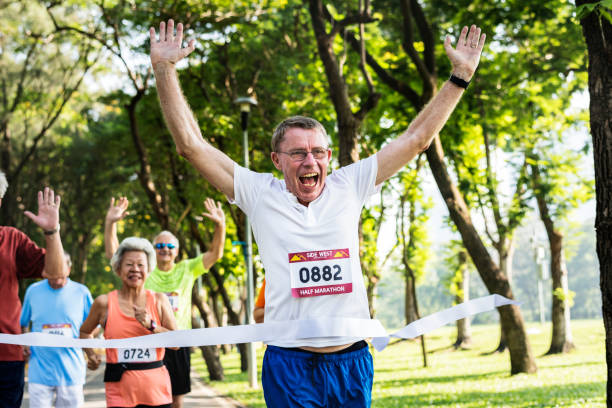 senior feliz corriendo a través de la línea de meta - maratón fotografías e imágenes de stock