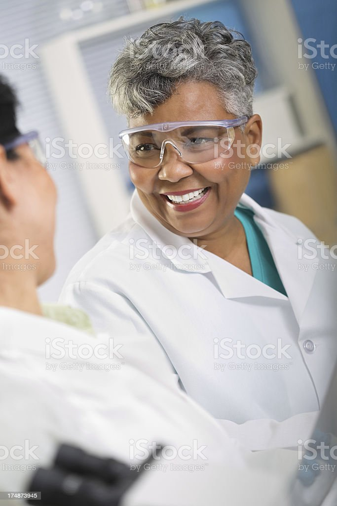 Happy senior scientist taking with colleague in science lab royalty-free stock photo