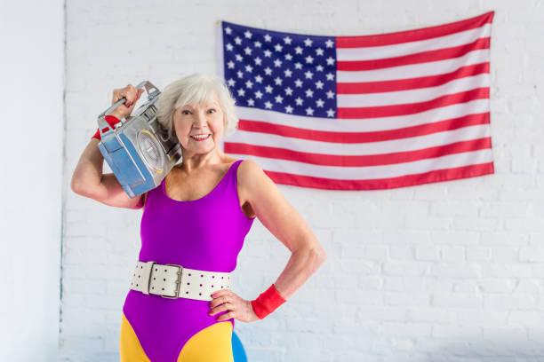 glücklich senior sportlerin holding tonbandgerät und lächelt in die kamera - 80er outfit stock-fotos und bilder