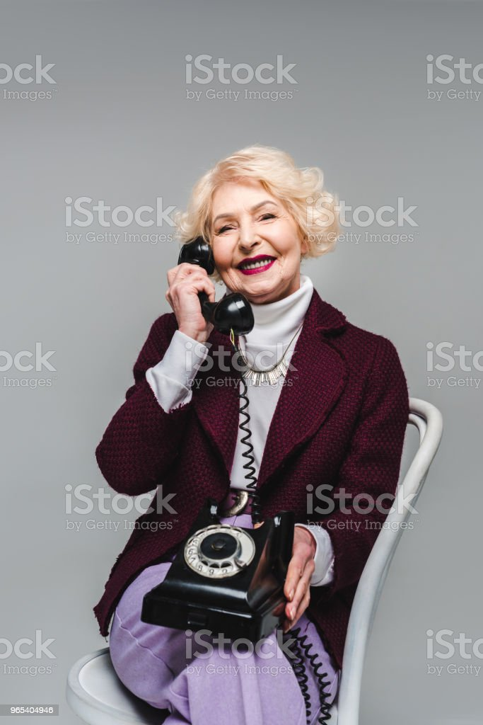 happy senior stylish woman sitting on chair and talking on rotary phone royalty-free stock photo