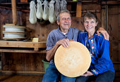 Couple of Swiss Cheesmakers Proudly Holding A Loaf Of Homemade Cheese. Cheese is made in this wooden farmhaus over open fire in a traditional way. Two more loafs of cheese are seen under the wooden press in the background. Taken in Lenk, Simmental, Bernese Oberland, Switzerland at Lenklypse 2012.