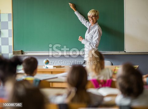 Happy senior teacher teaching elementary students on a class in the classroom and writing on blackboard. Copy space.