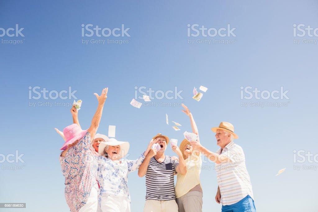 Happy senior throwing money stock photo