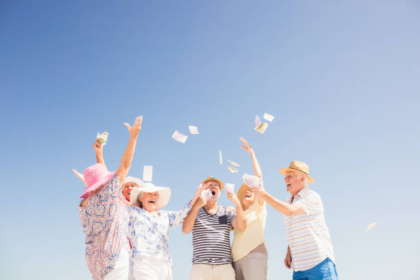 happy senior throwing money - throw money away stock pictures, royalty-free photos & images