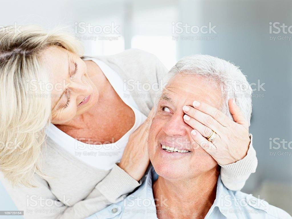 Happy senior wife covering eyes of her husband stock photo