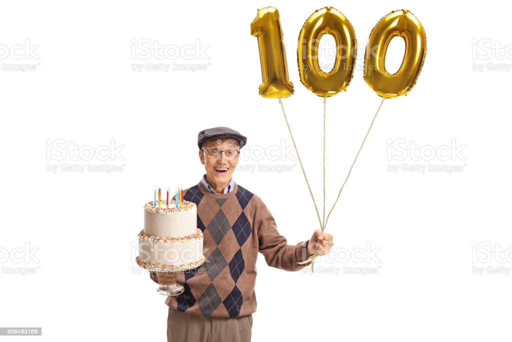 Happy senior with a birthday cake and a number hundred balloon stock photo