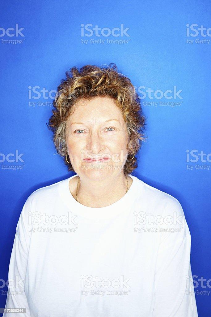 Happy senior woman against blue background royalty-free stock photo