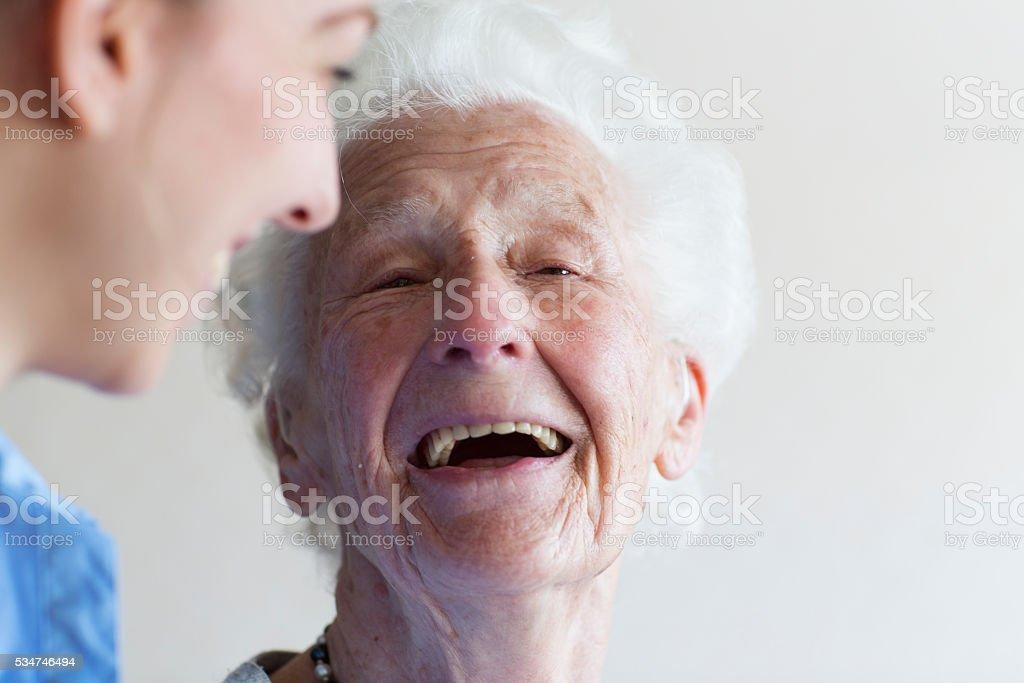 Happy senior woman and caregiver stock photo