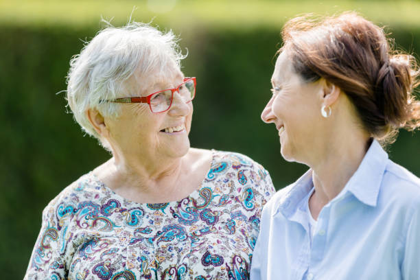 Glückliche Seniorin und Betreuerin zu Fuß im Freien – Foto