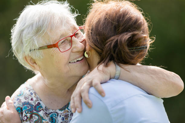 Happy senior woman and caregiver walking outdoors stock photo