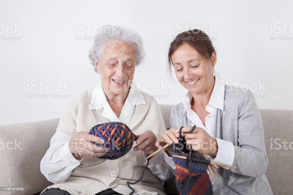 Happy senior woman and home caregiver in nursing home