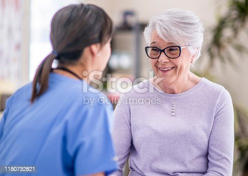 istock Happy senior woman at doctor's office 1150732821