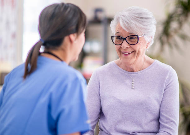 Happy senior woman at doctor's office A senior woman talks to her doctor about some recent struggles she is going through. She looks very optimistic. hormone stock pictures, royalty-free photos & images