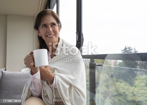 Happy senior woman at home enjoying a hot chocolate on a cold day looking at window view smiling - Flatten the curve