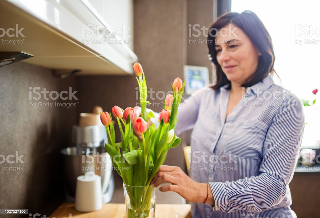 Happy senior woman at home putting flowers in a vase. royalty-free stock photo  sc 1 st  iStock & Happy Senior Woman At Home Putting Flowers In A Vase Stock Photo ...